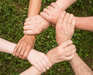 Kuvitus: Ihmiset pitävät kiinni toistensa käsistä, tiimityötä, opiskeleva asiantuntija osana työyhteisöä